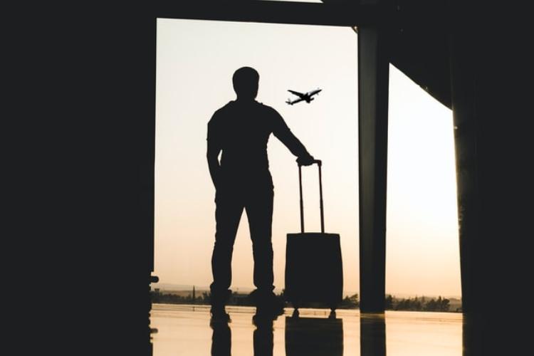 Čovek koji stoji na aerodromu sa koferom i vraća se u Beograd iz inostranstva.